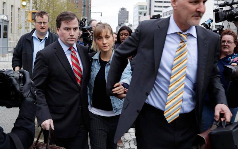 Allison Mack is escorted away from Federal court Tuesday, April 24, 2018, in Brooklyn, New York - AP