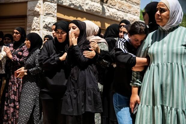 Mourners at the funeral of Israeli Arab Khalil Awaad and his daughter Nadine, 16, in the village of Dahmash near the Israeli city of Lod. A rocket fired from Gaza Strip hit their house and killed both.