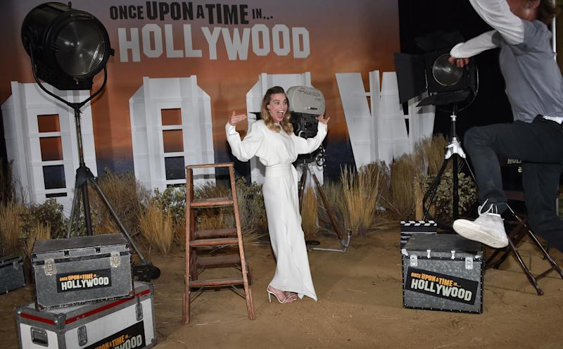 "Australian actress Margot Robbie laughs as US actor Brad Pitt tries to photobomb her during the photo call for Sony Pictures' ""Once Upon a Time in Hollywood"" at the Four Seasons hotel on July 11, 2019 in Los Angeles. (Photo by Chris Delmas / AFP) (Photo credit should read CHRIS DELMAS/AFP/Getty Images)"