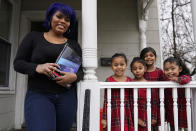 Dinora Torres, a MassBay Community College student, poses with her four daughters on the front porch of their home, Thursday, Jan. 14, 2021, in Milford, Mass. At the college, applications for meal assistance scholarships have increased 80% since last year. Among the recipients is Torres, who said the program helped keep her enrolled. From front left are daughters Davina, Alana and Hope, with Faith in Dinora's arms. (AP Photo/Charles Krupa)