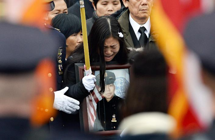 Pei Xia Chen, widow of New York Police Department officer Wenjian Liu, cries holding a picture of her husband during his funeral in New York's borough of Brooklyn on January 4, 2015 (AFP Photo/Jewel Samad)