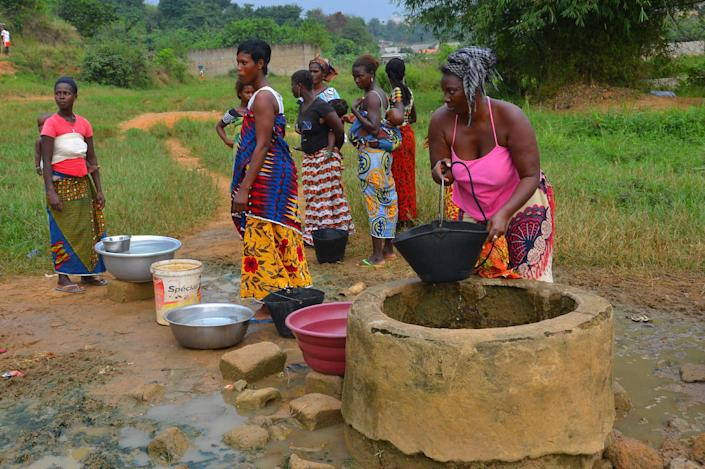 Women fetch water from a well near the site where two boys were attacked, in Yopougon, Ivory Coast, on January 26, 2015 (AFP Photo/Herve Sevi)