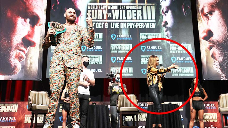 Tyson Fury (pictured left) poses with his belt as host Kate Abdo (pictured right) gestures on stage.