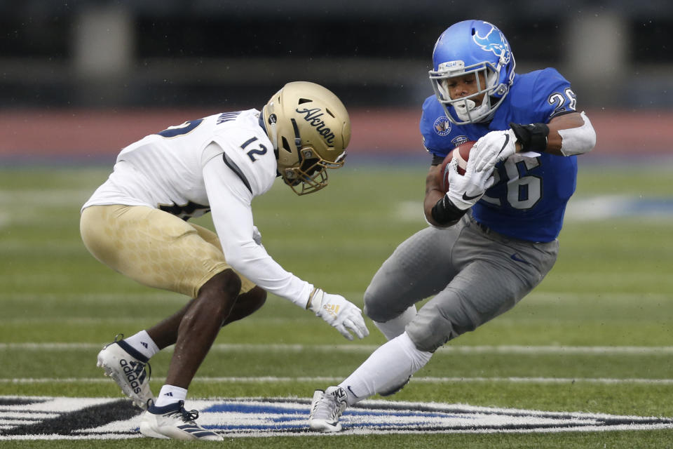 Buffalo running back Jaret Patterson (26)  is tackled by Akron's Charles Amankwaa (12) during the first half of an NCAA college football game at UB stadium in Amherst, N.Y., Saturday Dec. 12, 2020. (AP Photo/Jeffrey T. Barnes)