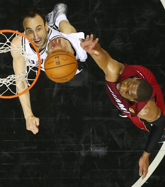 San Antonio Spurs guard Manu Ginobili, left, and Miami Heat guard Dwyane Wade go after the ball during Game 1 of the NBA basketball finals on Thursday, June 5, 2014 in San Antonio. (AP Photo/Andy Lyons, Pool)