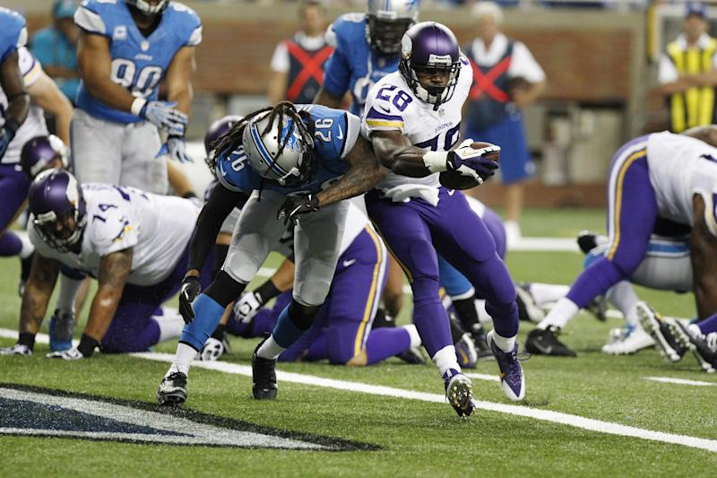 Minnesota Vikings running back Adrian Peterson (28), defended by Detroit Lions free safety Louis Delmas (26), runs into the end zone for a 4-yard touchdown during the second quarter of an NFL football game at Ford Field in Detroit, Sunday, Sept. 8, 2013. (AP Photo/Duane Burleson)
