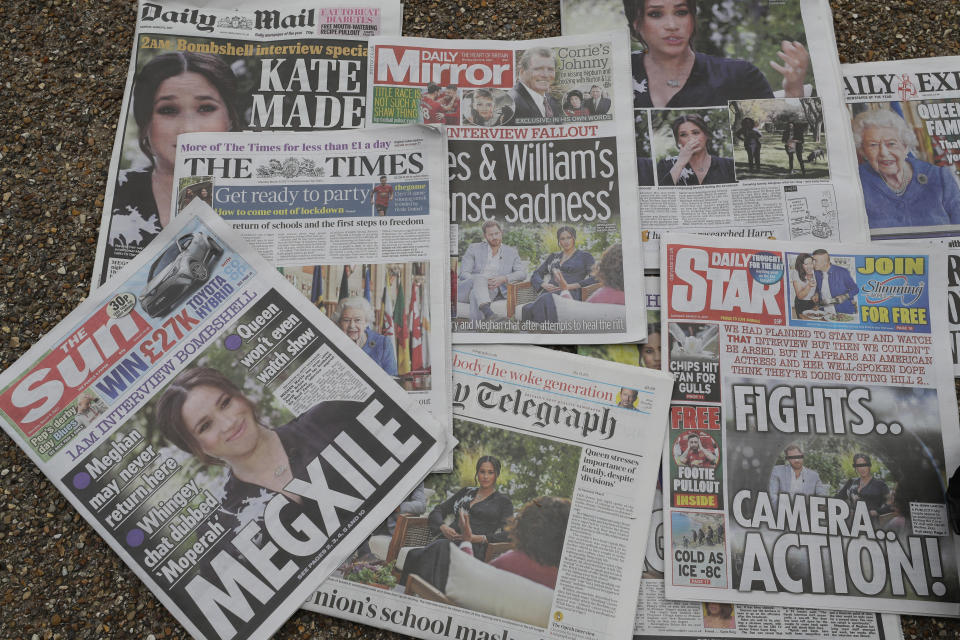 Newspapers are placed on the ground placed by a television crew in front of Buckingham Palace in London, Monday, March 8, 2021. Britain's royal family is absorbing the tremors from a sensational television interview by Prince Harry and the Duchess of Sussex, in which the couple said they encountered racist attitudes and a lack of support that drove Meghan to thoughts of suicide. (AP Photo/Kirsty Wigglesworth)
