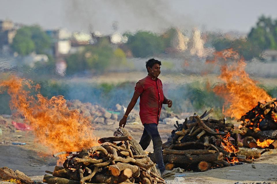 TOPSHOT - Funeral pyres burn as the last rites are performed of the patients who died of the Covid-19 coronavirus at a cremation ground in Allahabad on April 27, 2021. (Photo by SANJAY KANOJIA / AFP) (Photo by SANJAY KANOJIA/AFP via Getty Images)