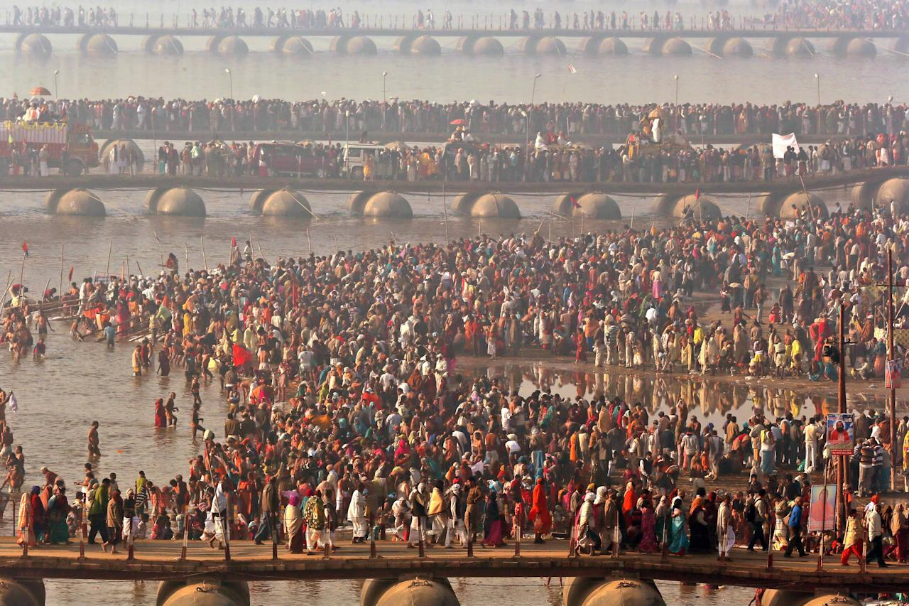 Hindu devotees walk across pontoon bridges to take a holy dip at Sangam, the confluence of the Ganges, Yamuna and mythical Saraswati River, during the Maha Kumbh festival, in Allahabad, India , Sunday, Feb. 10, 2013. Millions of devout Hindus and thousands of Hindu holy men are expected to take a dip at Sangam on Sunday, the most auspicious day according to the alignment of stars, for the entire duration of Maha Kumbh festival, which lasts for 55 days. (AP Photo /Manish Swarup)