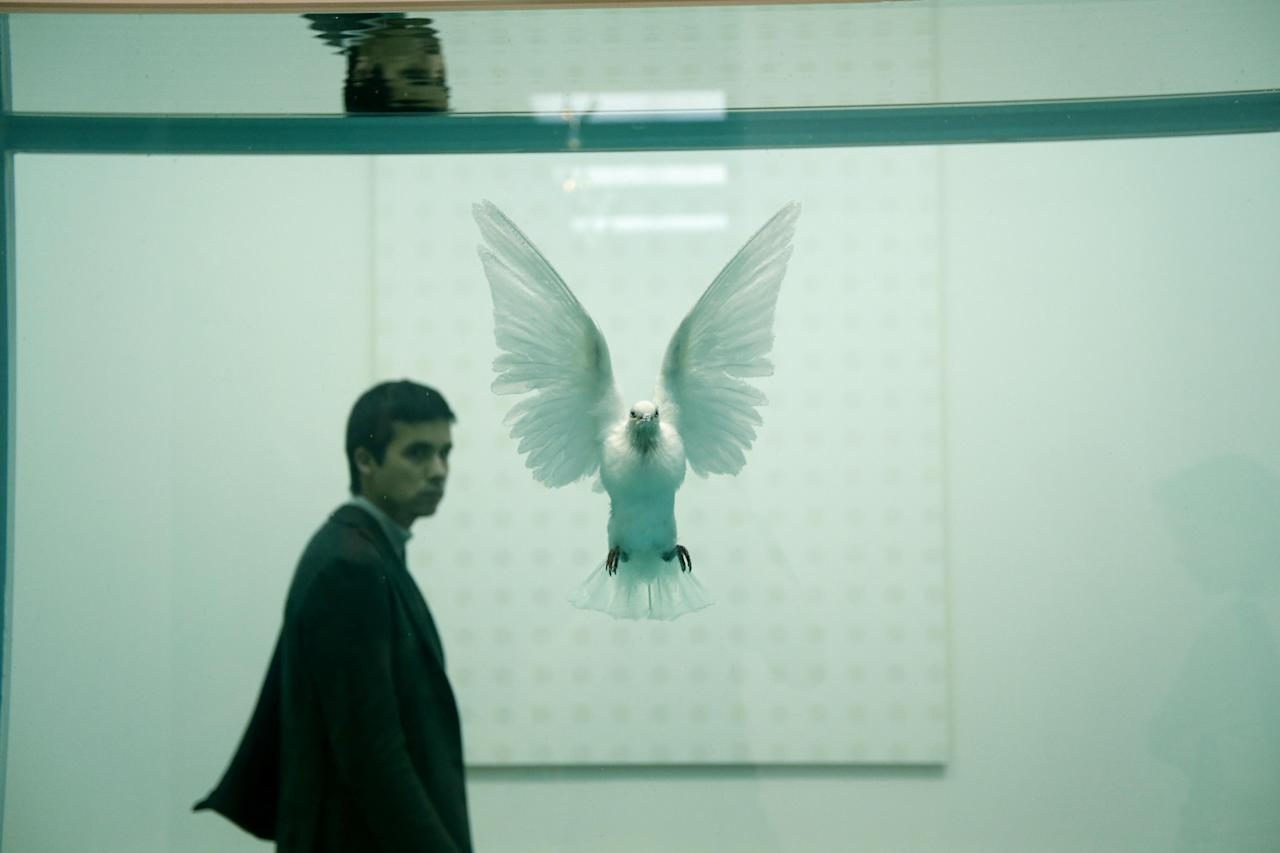 "A man walks past the British artist Damien Hirst's 2006 piece ""The Incomplete Truth"", a dove in a formaldehyde solution in a vitrine, during a media preview of the first substantial survey show of his work in the UK at the Tate Modern gallery in London, Monday, April 2, 2012. The exhibition, timed for the culmination of the Cultural Olympiad and due to open to the public on Wednesday, showcases over 70 of Hirst's works since he first came to public attention in 1988. (AP Photo/Matt Dunham)"
