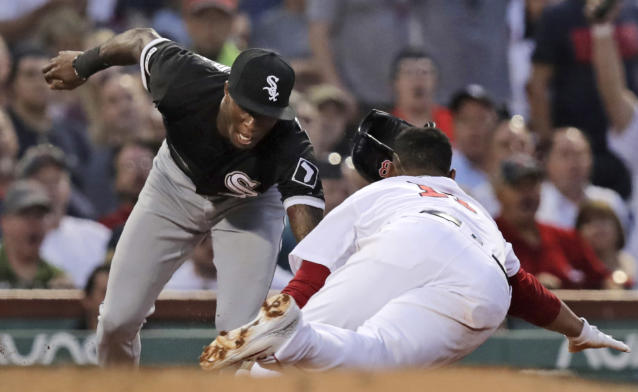 Chicago White Sox shortstop Tim Anderson, left, tags out Boston Red Sox's Rafael Devers, who was caught off third base, during the fourth inning of a baseball game at Fenway Park in Boston, Monday, June 24, 2019. (AP Photo/Charles Krupa)