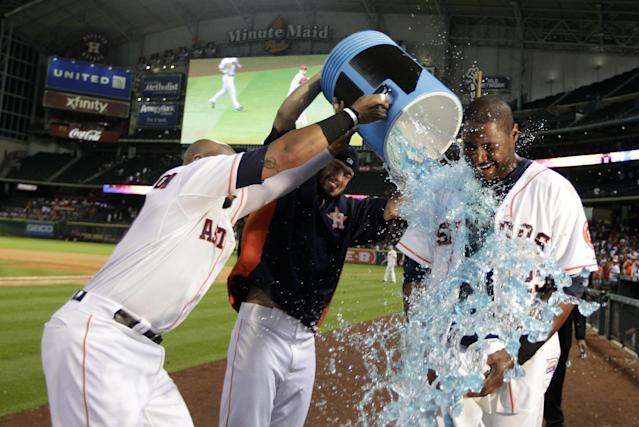 Houston Astros' Jon Singleton, left, and Jarred Cosart dump a water cooler on Chris Carter after Carter hit a walk off home run to defeat the Arizona Diamondbacks 5 - 4 during the 10th inning of a baseball game, Thursday, June 12, 2014, in Houston. (AP Photo/Patric Schneider)