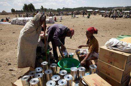 An elderly woman receives cooking oil at an emergency food aid distribution in the village of Estayish in Ethiopia's northern Amhara region