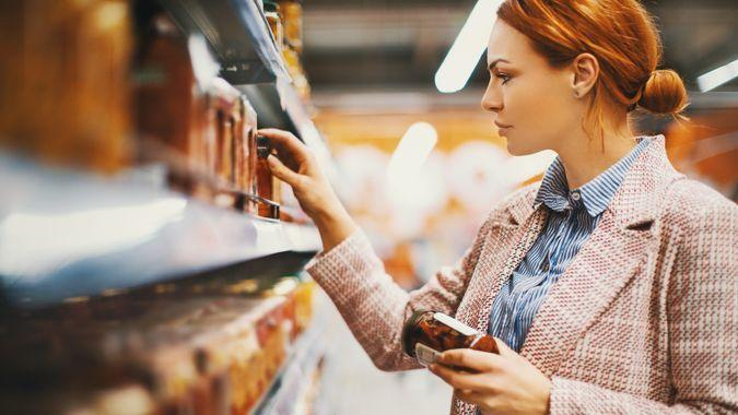 Young woman holding a jar of Sun-dried tomatoes in supermarket.
