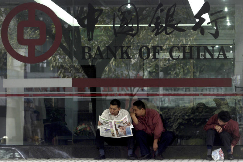 In this photo taken Tuesday, Jan 6, 2004, Chinese men share a newspaper outside a Bank of China branch in Guangzhou, southeastern China Guangdong province.  One of China's biggest banks said Tuesday, May 7, 2013 that it has halted business with the Foreign Trade Bank of North Korea accused by the U.S. of financing Pyongyang's missile and nuclear programs in the latest sign of Beijing's anger with its estranged ally.(AP Photo/Ng Han Guan)