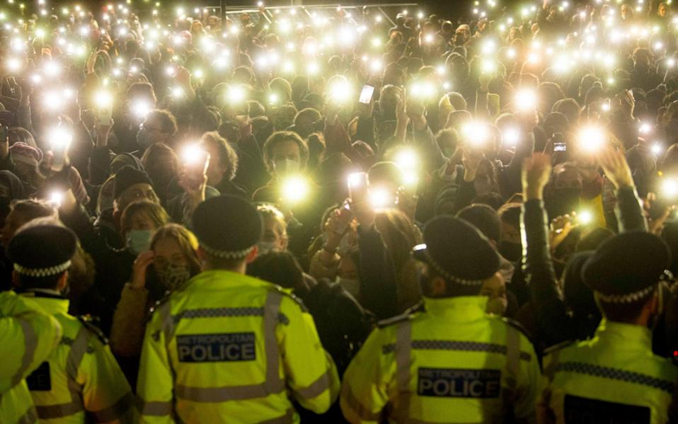 People in the crowd turned on their phone torches as they gathered in Clapham Common, London, after the Reclaim These Streets vigil for Sarah Everard was officially cancelled - Victoria Jones/PA