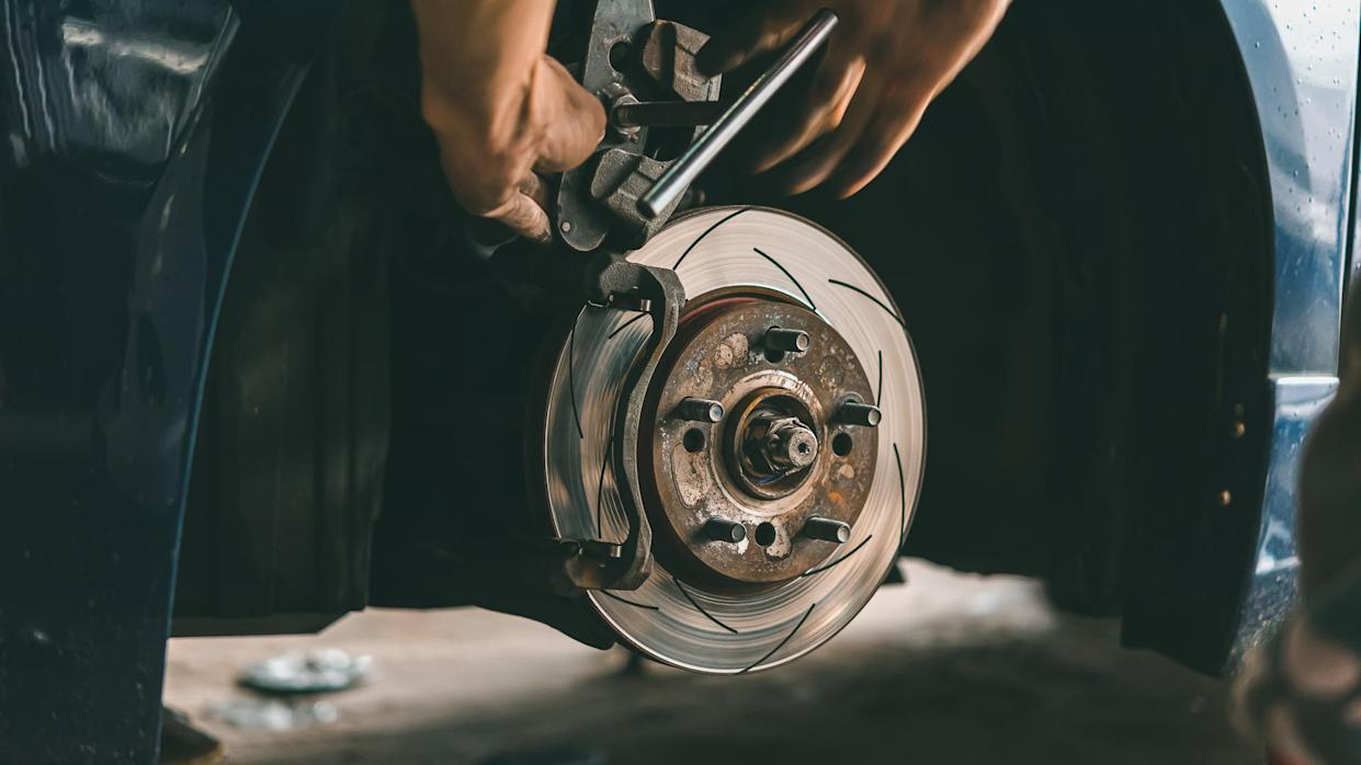 Car mechanic or serviceman checking a disc brake and asbestos brake pads it's a part of car use for stop the car for safety at front wheel this a new spare part for repair at car garage.