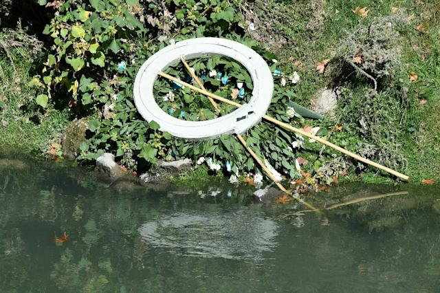 A floral wreath from the Lazio football club lies near the Tiber river after it disapeared from the wall of synagogue on October 25, 2017 in Rome; Lazio president Claudio Lotito had paid a visit, bringing a wreath to remember victims of anti-semitism (AFP Photo/Alberto PIZZOLI)