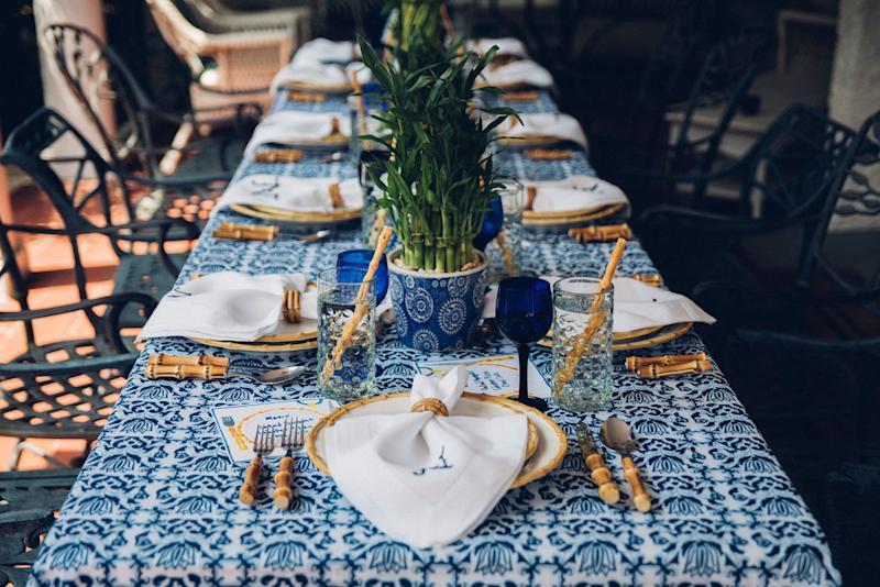 What's on her table: Chefanie Bamboo Napkin Rings, Chefanie Ceramic Bamboo Straws, Chefanie Blue & White tablecloth, Chefanie Custom Embroidered Linen Napkins, Juliska flatware, Juliska plates , fresh bamboo plants from Home Depot, and her mother's blue and white urns.