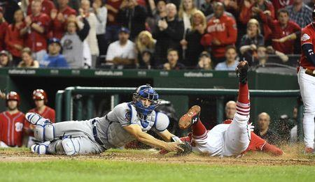 May 19, 2018; Washington, DC, USA; Washington Nationals first baseman Mark Reynolds (14) slides to score a run beating the tag attempt by Los Angeles Dodgers catcher Austin Barnes (15) during the sixth inning at Nationals Park. Mandatory Credit: Brad Mills-USA TODAY Sports
