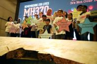 Family members of the victims pose for a group picture with a debris of the missing Malaysia Airlines flight MH370 during its sixth annual remembrance event in Putrajaya