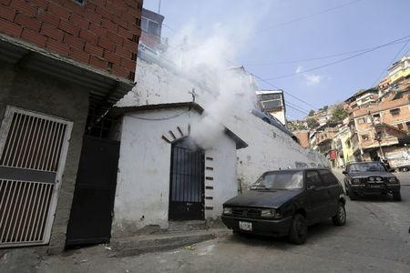 A insecticide smoke is seen coming out a chapel as Venezuelan health workers fumigate the Valle slum to help control the spread of the mosquito-borne Zika virus in Caracas, January 28, 2016. REUTERS/Marco Bello