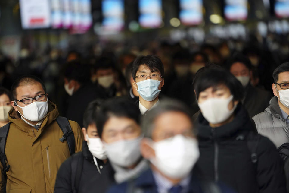 Some people commute on the first business day of the year at a train station Monday, Jan. 4, 2021, in Tokyo. Japanese Prime Minister Yoshihide Suga said Monday vaccine approval was being speeded up and border controls beefed up to curb the spread of the coronavirus, and he promised to consider declaring a state of emergency.(AP Photo/Eugene Hoshiko)