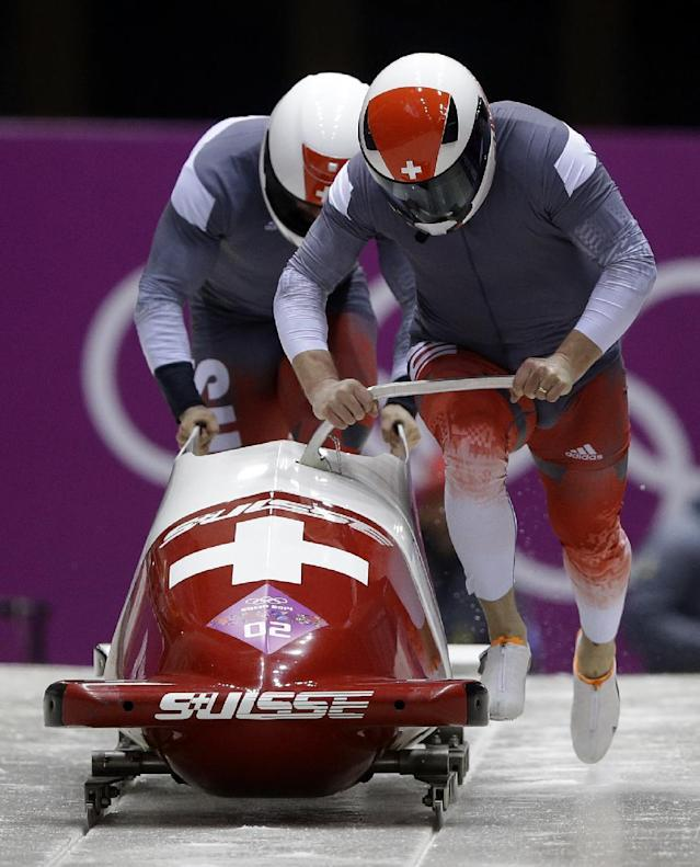 The team from Switzerland SUI-1, piloted by Beat Hefti and brakeman Alex Baumann, start their first run during the men's two-man bobsled competition at the 2014 Winter Olympics, Sunday, Feb. 16, 2014, in Krasnaya Polyana, Russia. (AP Photo/Dita Alangkara)