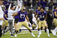 Washington players and coaches celebrate beating California in an NCAA college football game Saturday, Sept. 25, 2021, in Seattle. Washington won 31-24 in overtime. (AP Photo/Elaine Thompson)