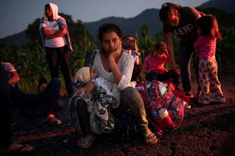 A migrant woman rests roadside with her child while traveling with a caravan of thousands from Central America en route to the U.S. (Yahoo News Photo Staff)