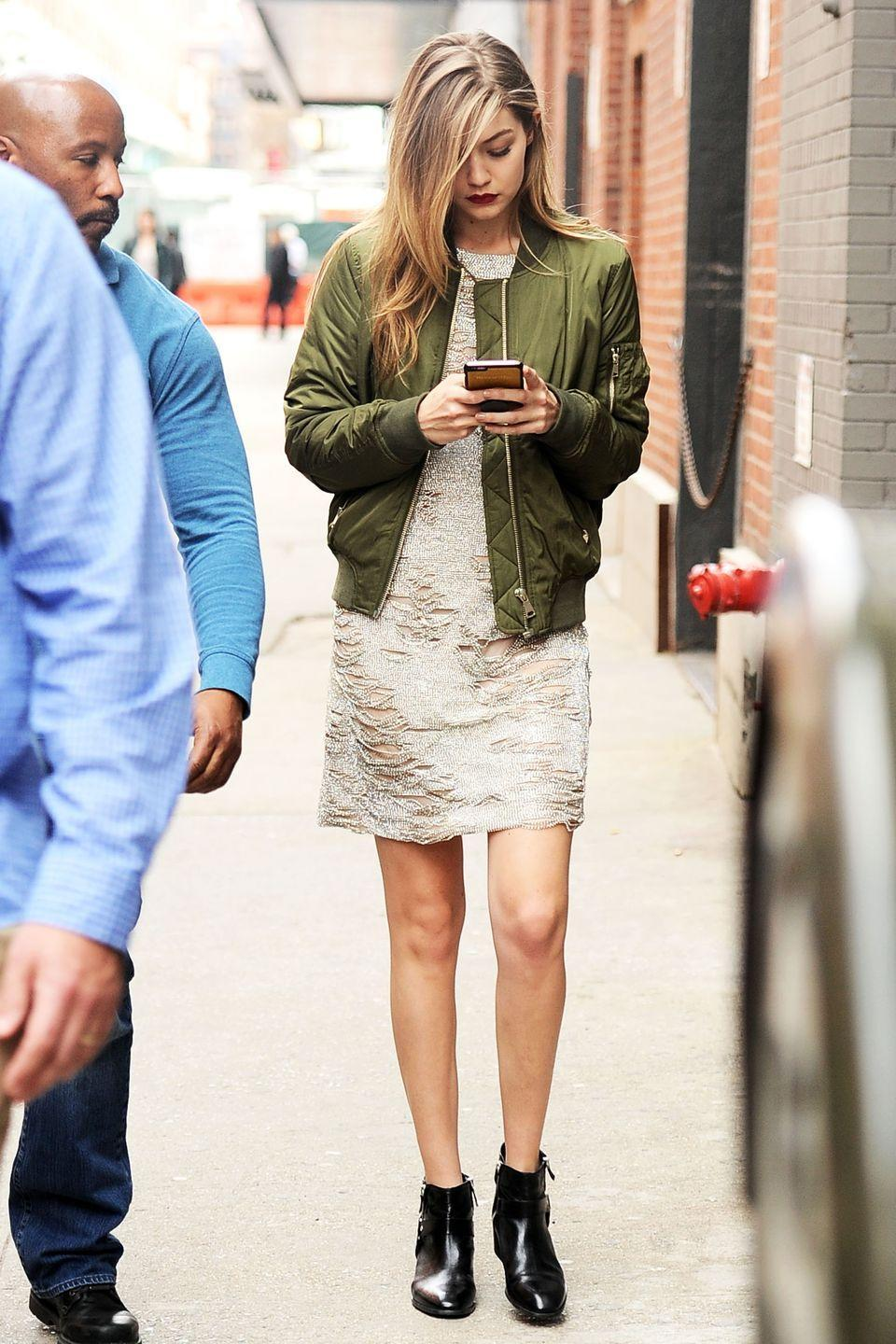 <p>The model looked chic in an embellished dress with distressed touches, paired with an on-trend olive green bomber jacket and black booties. </p>