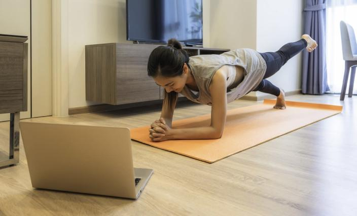 Young fit beautiful Asian woman in sportswear workout exercise (plank) in living room on yoga mat with laptop. Workout from home and online training concept during Covid 19 pandemic outbreak