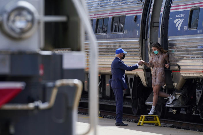 President Joe Biden offers his granddaugther Finnegan Biden a hand as she steps off a train car during an event to mark Amtrak's 50th anniversary at 30th Street Station in Philadelphia, Friday, April 30, 2021. (AP Photo/Patrick Semansky)