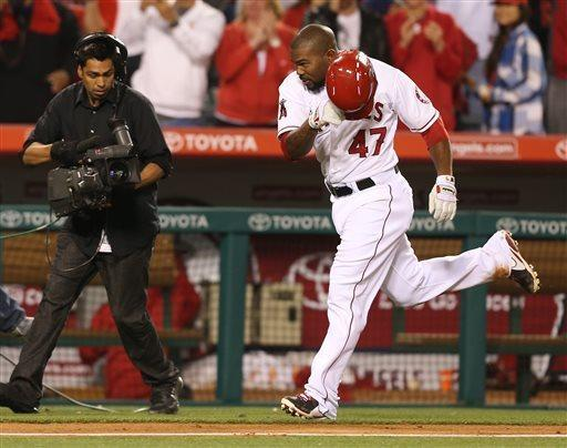 Los Angeles Angels Howie Kendrick begins to celebrate after a solo home run to beat the Texas Rangers 5-4 in the eleventh inning of a baseball game in Anaheim, Calif., on Tuesday, April 23, 2013. (AP Photo/Christine Cotter)