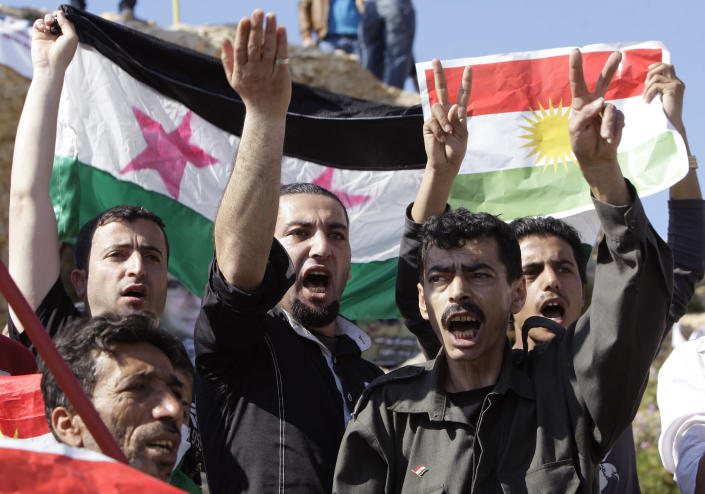 Syrian Kurds citizens who live in Lebanon and opposed to Syrian President Bashar Assad, hold up a Kurdish flag, right, and a Syrian revolution flag, left, chant slogans against the Syrian regime as they celebrate the Nowruz day in Beirut, Lebanon, Wednesday, March 21, 2012. The U.N. Security Council has strongly backed international envoy Kofi Annan's proposals to end the yearlong bloodshed in Syria. (AP Photo/Bilal Hussein)