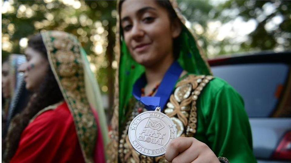 One of the Afghan team members at the 2017 International Robotics Championship shows her medal