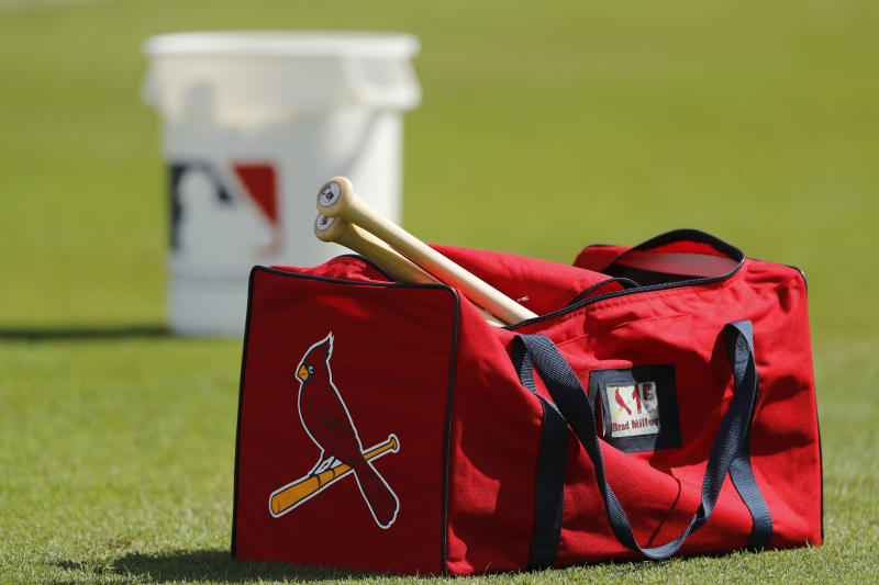 A St. Louis Cardinals duffel bag sits on a baseball field.
