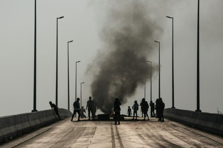 Protesters stand near burning tyres during a crackdown by security forces on demonstrations in Yangon