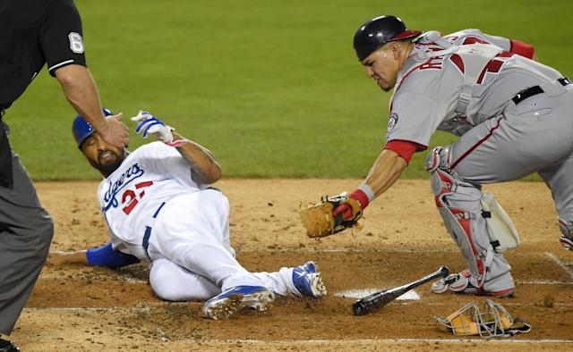 Los Angeles Dodgers' Matt Kemp, center, is tagged out at home by Washington Nationals catcher Wilson Ramos as he tried to score on a bunt by Carl Crawford during the fourth inning of a baseball game Tuesday, Sept. 2, 2014, in Los Angeles. (AP Photo/Mark J. Terrill)