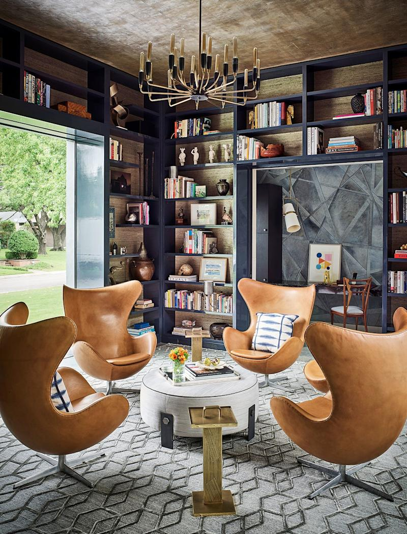 SHM Architects and designer Jay Jeffers collaborated on the Dallas home of Juliette and Mark Moussa, the founder of Arteriors (arteriorshome.com); the chandelier and accent tables are by Arteriors, the chairs are vintage Arne Jacobsen, and the bookcases are backed in Phillip Jeffries wallpaper.