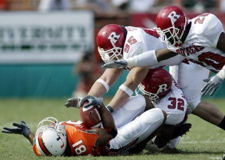 University of Miami Hurricanes' tight end Kellen Winslow Jr. (L) is gang tackled after a reception by Rutgers University defenders Jarvis Johnson (R), Gary Gibson (95) and Nathan Jones (32) in the first half at the Orange Bowl in Miami, Florida, November 22, 2003. REUTERS/Marc Serota