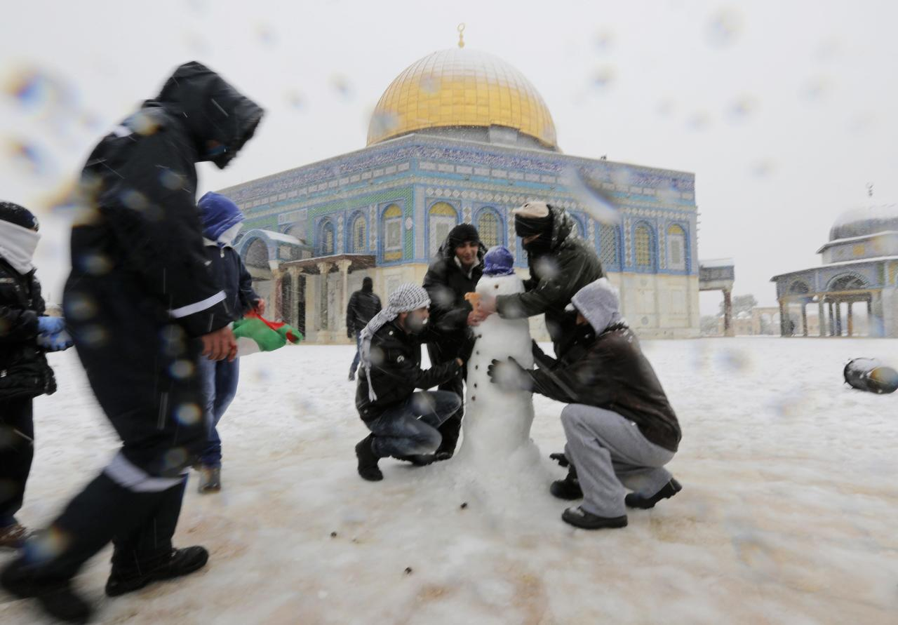 People build a snowman in front of the Dome of the Rock in the compound known to Muslims as Noble Sanctuary and to Jews as Temple Mount, in Jerusalem's Old City December 12, 2013. Snow fell in Jerusalem and parts of the occupied West Bank where schools and offices were widely closed and public transport was paused. REUTERS/Ammar Awad (JERUSALEM - Tags: RELIGION ENVIRONMENT)