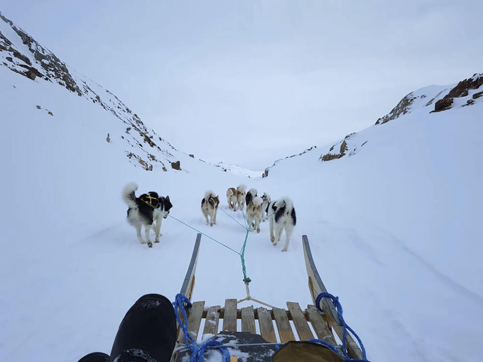 """In this Feb. 11, 2021, photo, provided by Lars Rasmussen, dogs pull him on a sled in the eastern Greenland town of Tasiilaq. """"The warm weather makes dog sledding and driving on snow scooters a bit of a hassle,"""" Rasmussen said. (Lars Rasmussen via AP)"""