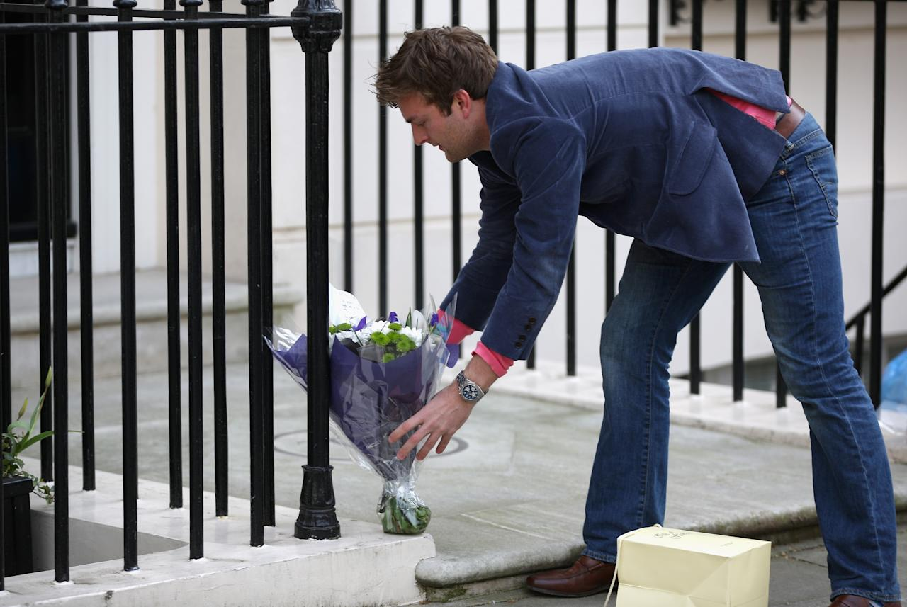 LONDON, ENGLAND - APRIL 08:  A man leaves a floral tribute outside the residence of Baroness Thatcher in Chester Square on April 8, 2013 in London, England. Lord Bell, spokesperson for Baroness Margaret Thatcher, announced in a statement that the former British Prime Minister died peacefully following a stroke on 8th April, aged 87.  (Photo by Peter Macdiarmid/Getty Images)