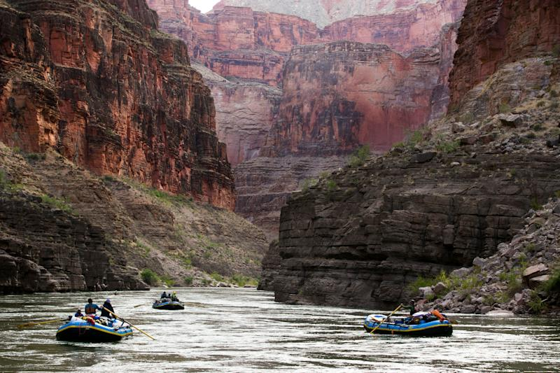 Boats make their way down the Colorado River near river mile 151 in Grand Canyon National Park. Before Glen Canyon Dam went in, in the waters of Colorado River would flow a reddish-brown color from all the silt. Now, because of the dam, the water is a clearer bluish/green, as the silt does not get past the dam.