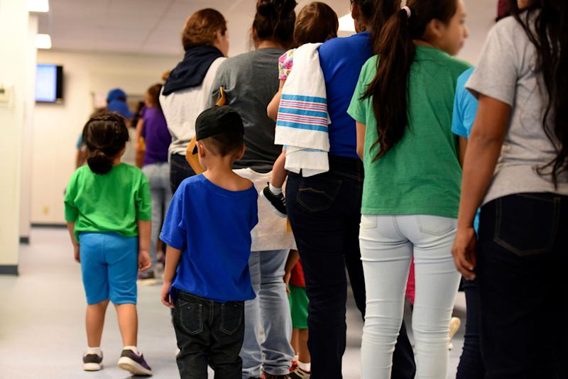 In this Aug. 9, 2018 photo provided by U.S. Immigration and Customs Enforcement, mothers and their children stand in line at South Texas Family Residential Center in Dilley, Texas. The family detention center is run as a for-profit business by CoreCivic, the country's largest private prison contractor. (Photo: ASSOCIATED PRESS)