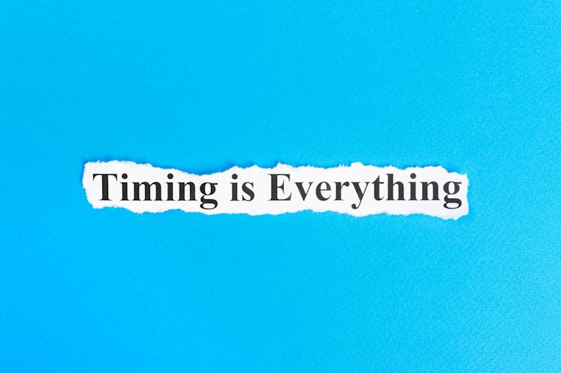 "A torn piece of white paper is set against a blue background and it has the words ""Timing is Everything"" printed on it."