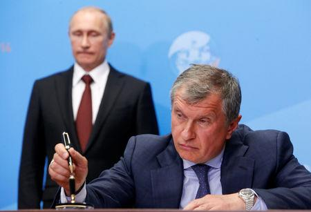 FILE PHOTO: Russia's President Vladimir Putin (L) and Rosneft CEO Igor Sechin attend a signing ceremony at the St. Petersburg International Economic Forum 2014 in St. Petersburg, Russia, May 24, 2014.   REUTERS/Sergei Karpukhin/File Photo