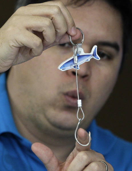 Angelo Villagomez of the PEW Environment Group shows a sample of a line and hook used to catch tuna during a press conference before the opening of the 9th regular session of the Western and Central Pacific Fisheries Commission in suburban Manila, Philippines on Sunday Dec. 2, 2012. Several governments and environmentalists have raised an alarm over destructive fishing methods and overfishing that were threatening the Pacific Ocean's bigeye tuna, the fish popular among sushi lovers the world over. (AP Photo/Aaron Favila)