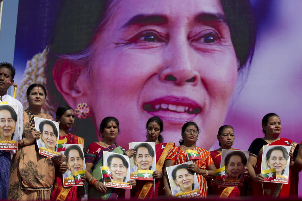 In this Dec. 10, 2019, file photo, members of Myanmar Hindu community hold portraits of Myanmar leader Aung San Suu Kyi to pray as they gather in front of City Hall for a rally in Yangon, Myanmar. After Myanmar's military staged a coup Monday, Feb. 1, 2021, Aung San Suu Kyi finds herself back under house arrest. But this time, her standoff with the generals comes after she has sorely disappointed many once-staunch supporters in the international community. (AP Photo/Thein Zaw, File)